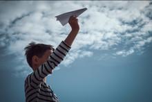 Boy Throwing White Paper Plane.