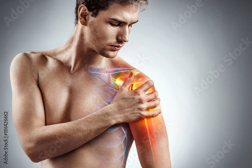 Fotomural Man holding his injured shoulder that's highlighted in red