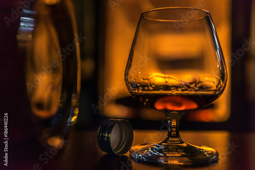 Staande foto Alcohol Time to enjoy! A glass filled with cognac stands on a table next to a cognac bottle. In the background a fireplace. Focus is on the bottle cap. Concept: drink or health