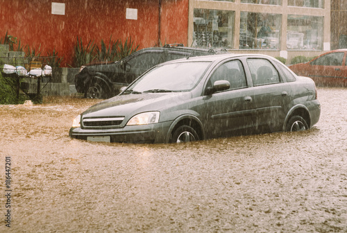 Fotografia, Obraz Unidentifiable passengers stuck in a car during heavy rains and flash flood - in