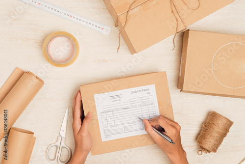 Fotografía  Top view of deliveryman making notes in delivery receipt at table