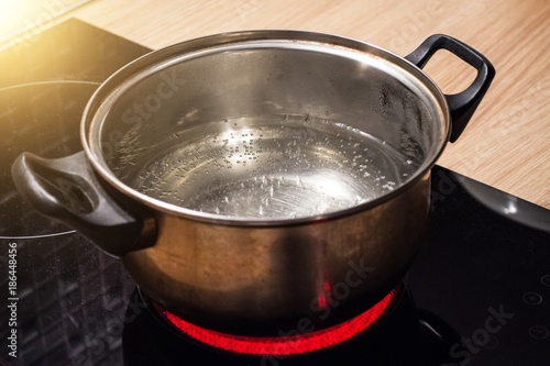 Metal pan with boiling water on the induction cooker red hot plate Fototapet