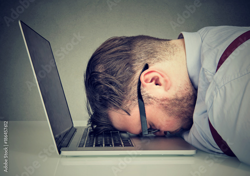 Photo  Overworked man lying on laptop