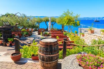 BOL TOWN, BRAC WYSPA - SEP 14, 2017: Tradycyjna restauracja dekorująca z kwiatami i wino baryłkami z dennym widokiem w Bol miasteczku, Brac wyspa, Chorwacja.