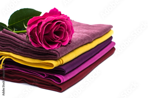 Fotografie, Obraz Red rose is laying on tippet scarf stack isolated on white background