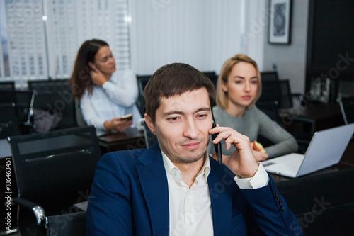 Fototapeta Young confident businessman talking by phone at office obraz na płótnie