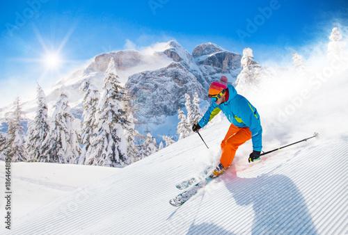 Fotobehang Wintersporten Skier skiing downhill in high mountains