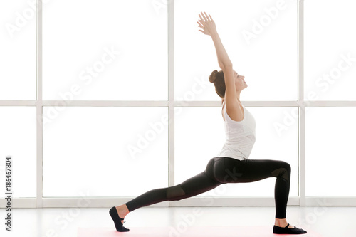 Fotografía  Woman looking up, hands up and doing yoga, warrior one posture