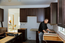 Carpenter Installing Cabinets ...