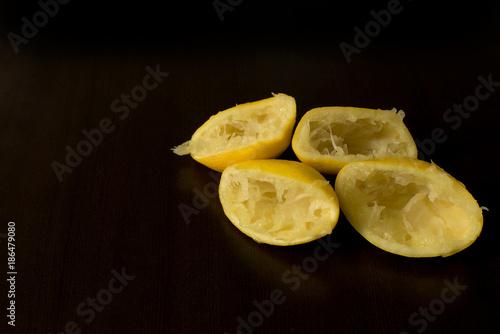 Fotografie, Obraz  Squeezed lemon skins on dark background - lemon peel - dark food photography, co