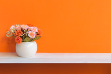 Orange Wall With Flowers On Sh...