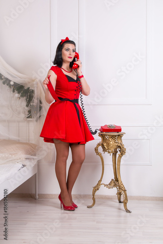 Pretty woman pin up style woman in vintage red dress and stockings.  Portrait in pin b617d6a7dbbc