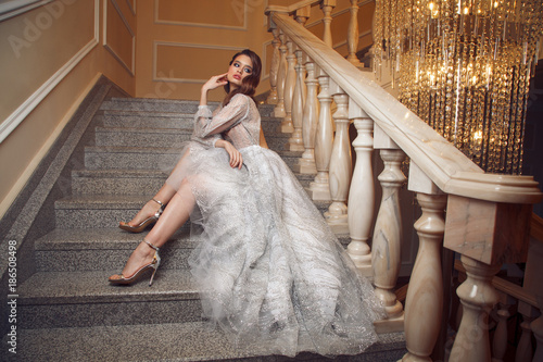 Full lenght portrait of gorgeous woman in the long silver dress on stairs Fototapet