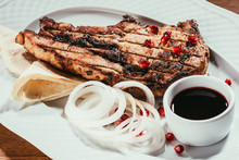 Close-up View Of Grilled Meat With Onion And Pomegranate Seeds On White Plate