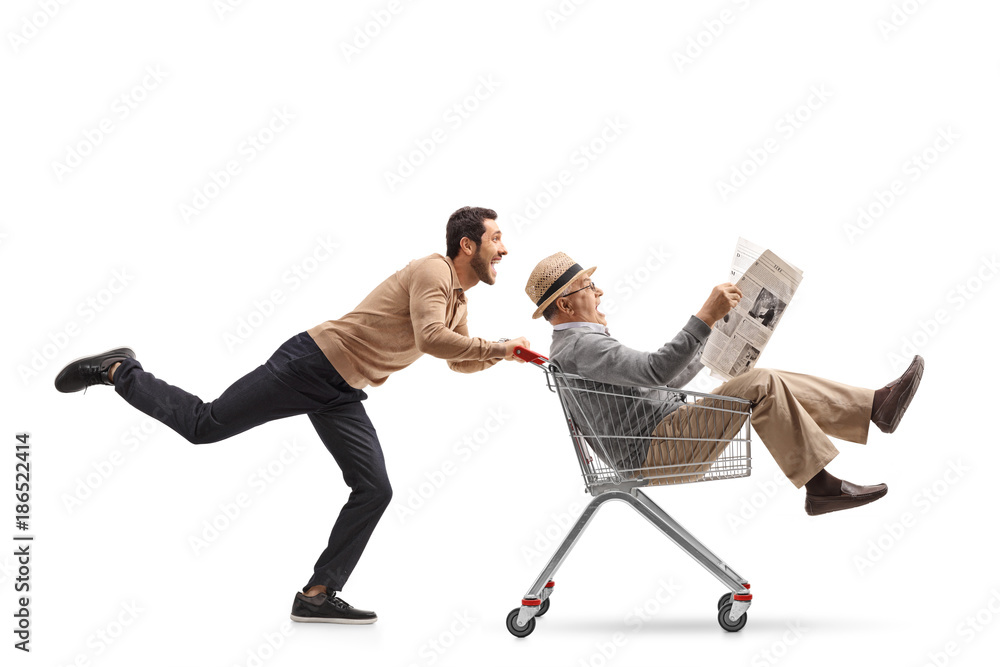 Fototapety, obrazy: Mature man with a newspaper riding inside a shopping cart being pushed by a young man