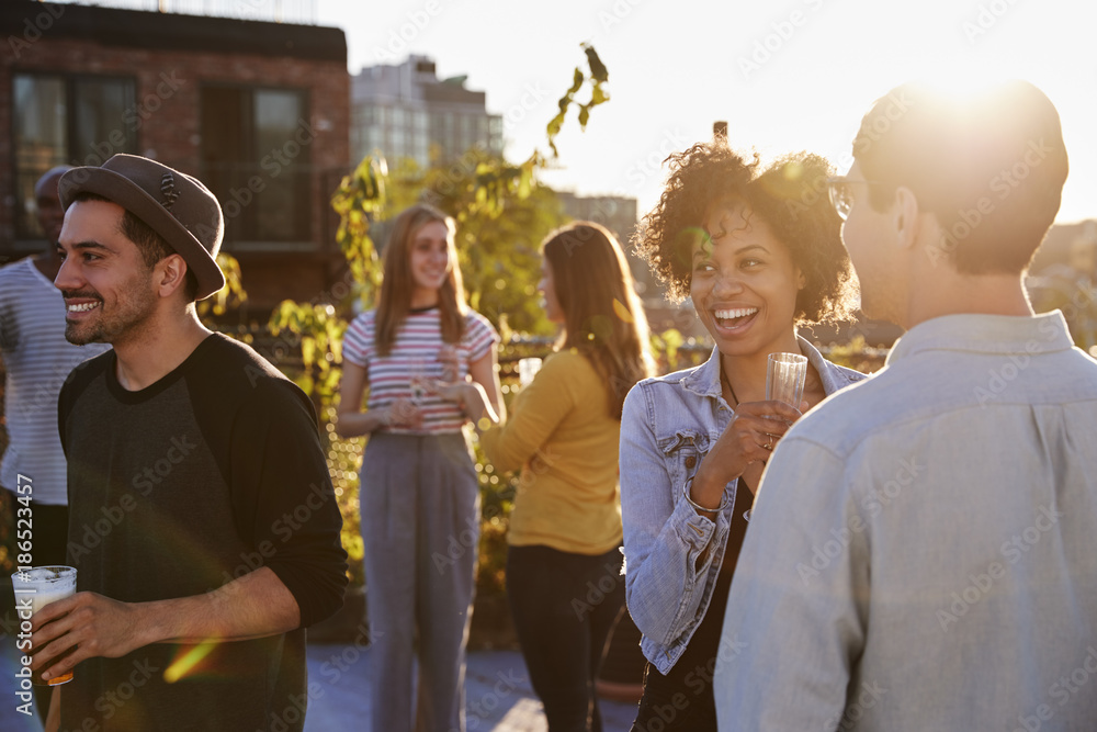 Fototapety, obrazy: Happy friends at a rooftop party backlit by sunlight