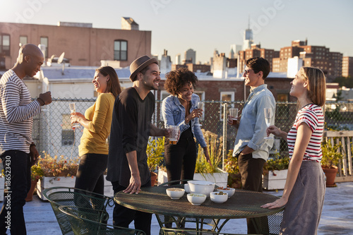 Fotografía  Friends stand talking at a party on a New York rooftop
