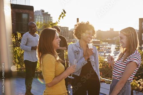Female friends talking at a rooftop party, backlit Fotobehang