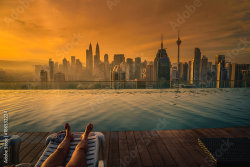 Traveler woman sleep on the sun bed near swimming pool on the roof top of hotel at sunrise in Kuala Lumpur, Malaysia.
