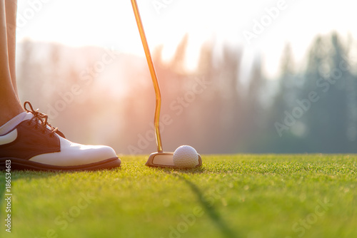 Poster Golf Golfer asian woman putting golf ball on the green golf on sun set evening time. Healthy and Lifestyle Concept.