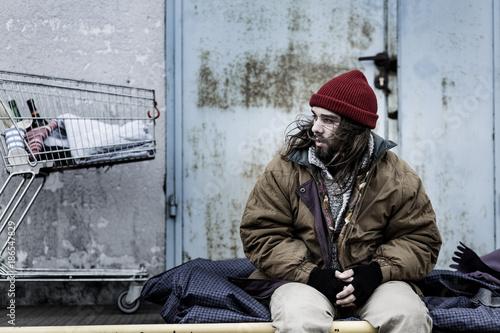 Fotografía  Dirty beggar sitting on night-bag