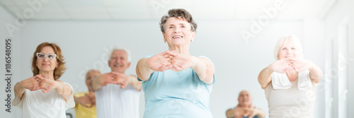 Smiling elderly woman stretching