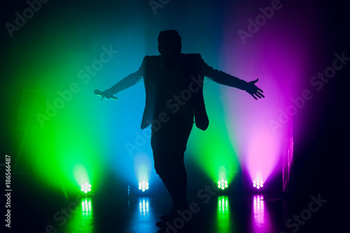 The entertainer. Young elegant talking man holding microphone Fototapet