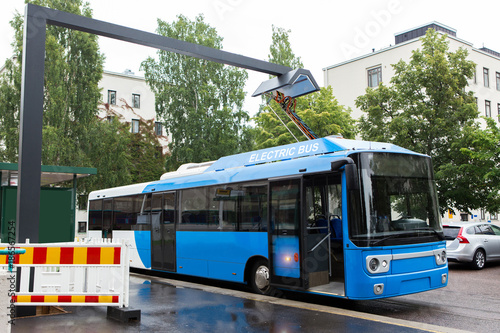Vászonkép Electric bus at a stop is charged by pantograph