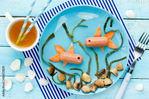 Fotografie, Obraz  Funny lunch for child - fish sausage with mushrooms and seaweed on a blue plate