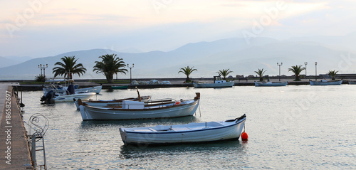 Deurstickers Australië Set of white vintage wood boats on sea with mountain background during sunset