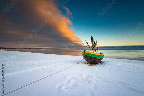 Fishing boat at snow covered beach in Sopot. Winter landscape. Poland.