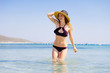Young girl in a hat bathes in the sea