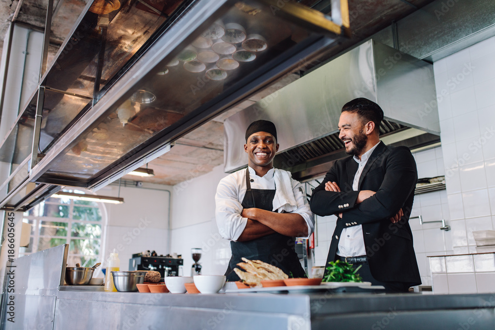 Fototapety, obrazy: Smiling restaurant owner and chef standing in kitchen