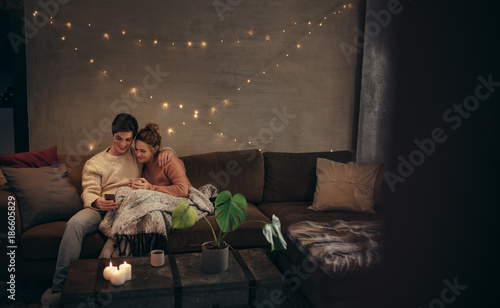 Valokuvatapetti Couple relaxing with smartphone in cozy living room