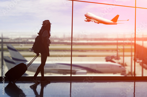 Young woman is standing near window at the airport and watching plane before departure.