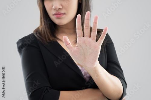 Valokuva  Business woman in black suit showing her denial with no on her hand against gray