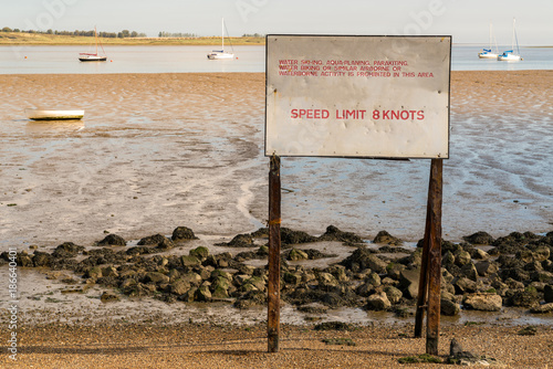 Fotografía  Sign: Speed limit 8 knots, with some boats and the Isle of Sheppey in the backgr