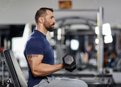 Man doing biceps curl in the gym Canvas Print