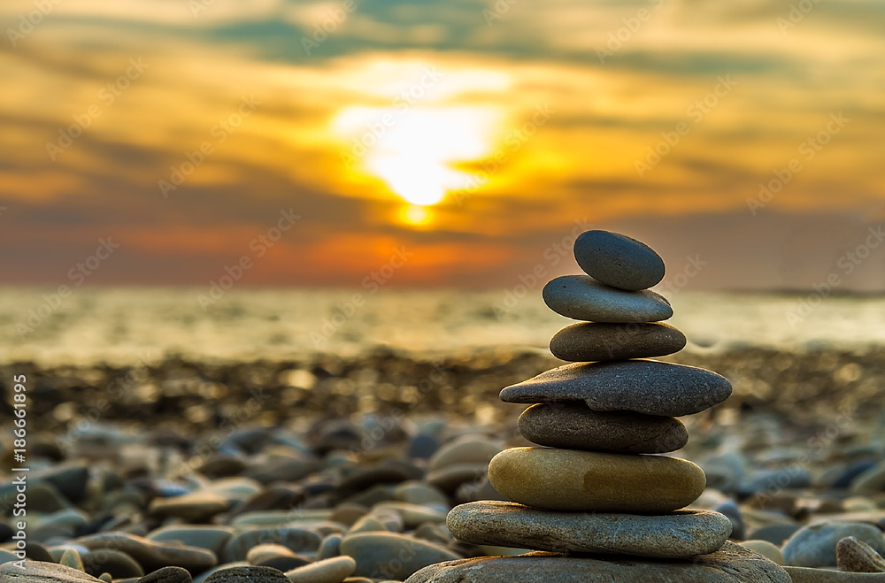 Fototapety, obrazy: pyramid of stones on the background of sunset at sea