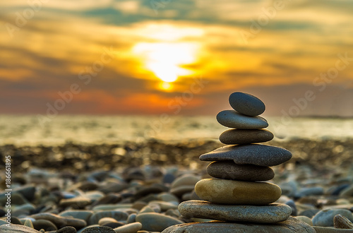 Leinwand Poster pyramid of stones on the background of sunset at sea