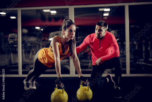 Fotografía Close up of motivated focused attractive young woman doing push ups exercise on the kettlebells in the gym with her handsome muscular personal trainer