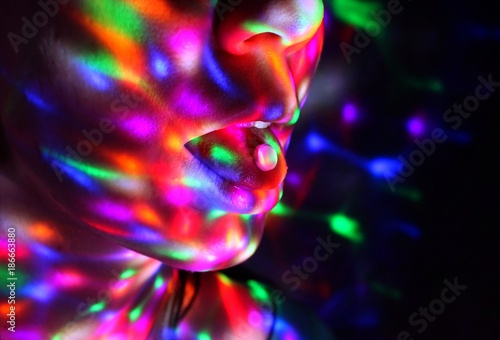 A young woman has ecstasy on her tongue in a night club. Fototapete