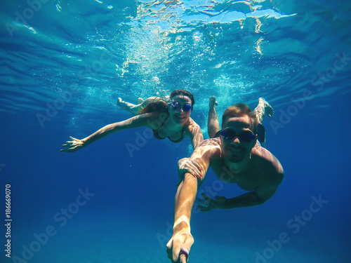 Underwater selfie with a stick of a happy handsome love couple swimming in the turquoise sea under the surface for summer vacation.