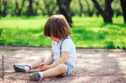 Valokuvatapetti cute little toddler child boy playing with dirt and sitting on the ground on the