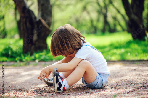 cute little toddler child boy playing with dirt and sitting on the ground on the Tablou Canvas