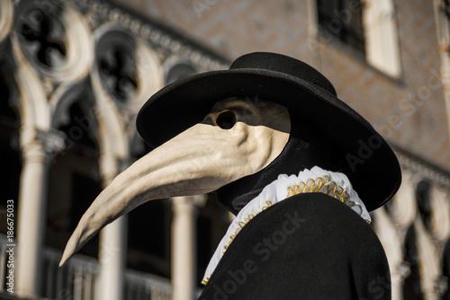Fototapeta premium Plague Doctor Mask, tradycyjny wenecki kostium karnawału weneckiego, z gotycką dekoracją w tle Pałacu Dożów