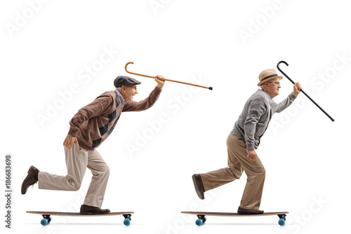 Two elderly men with canes riding longboards