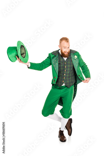 Fototapeta handsome leprechaun in green costume holding hat, isolated on white