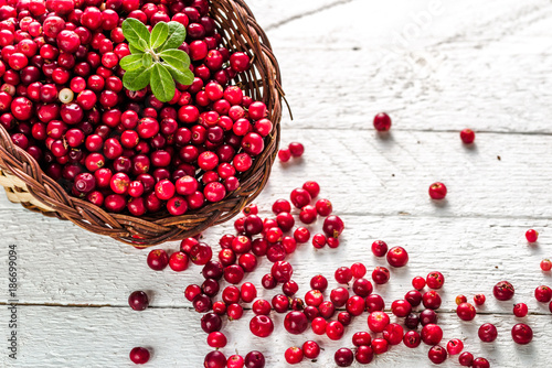 Fotografia  Basket of fresh cranberry on wooden table, red berries also called cowberry or l