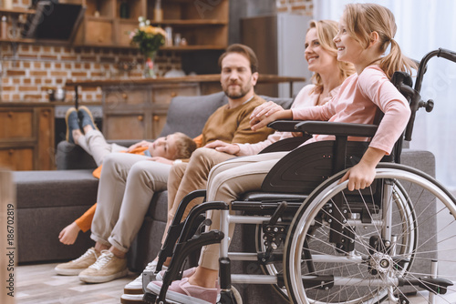 Obraz happy family with disabled little daughter in wheelchair spending time together at home - fototapety do salonu